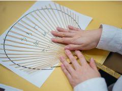 竹の骨と和紙を型紙にあわせてうちわの形に切り取ります。