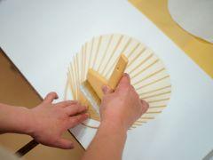 うちわの骨に糊をつけて和紙を貼ります。