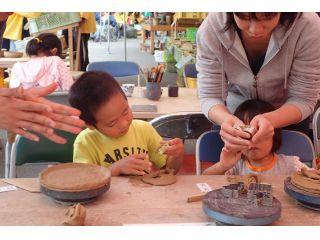 粘土を手でこねながら、器を形作る手びねり作業。