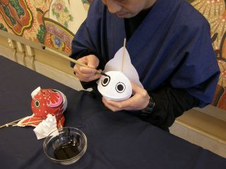 墨で金魚の目を描いています