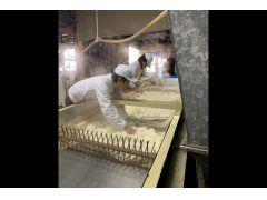 蒸された酒米がコンベアで冷まされながら流れていきます。