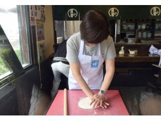 手のひらと麺棒を使ってうどん生地を伸ばします